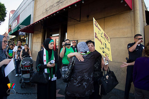 Syria protestors from opposite sides hug outside of the Arpa International Film Festival at Grauman's Egyptian Theatre in Los Angeles, California.